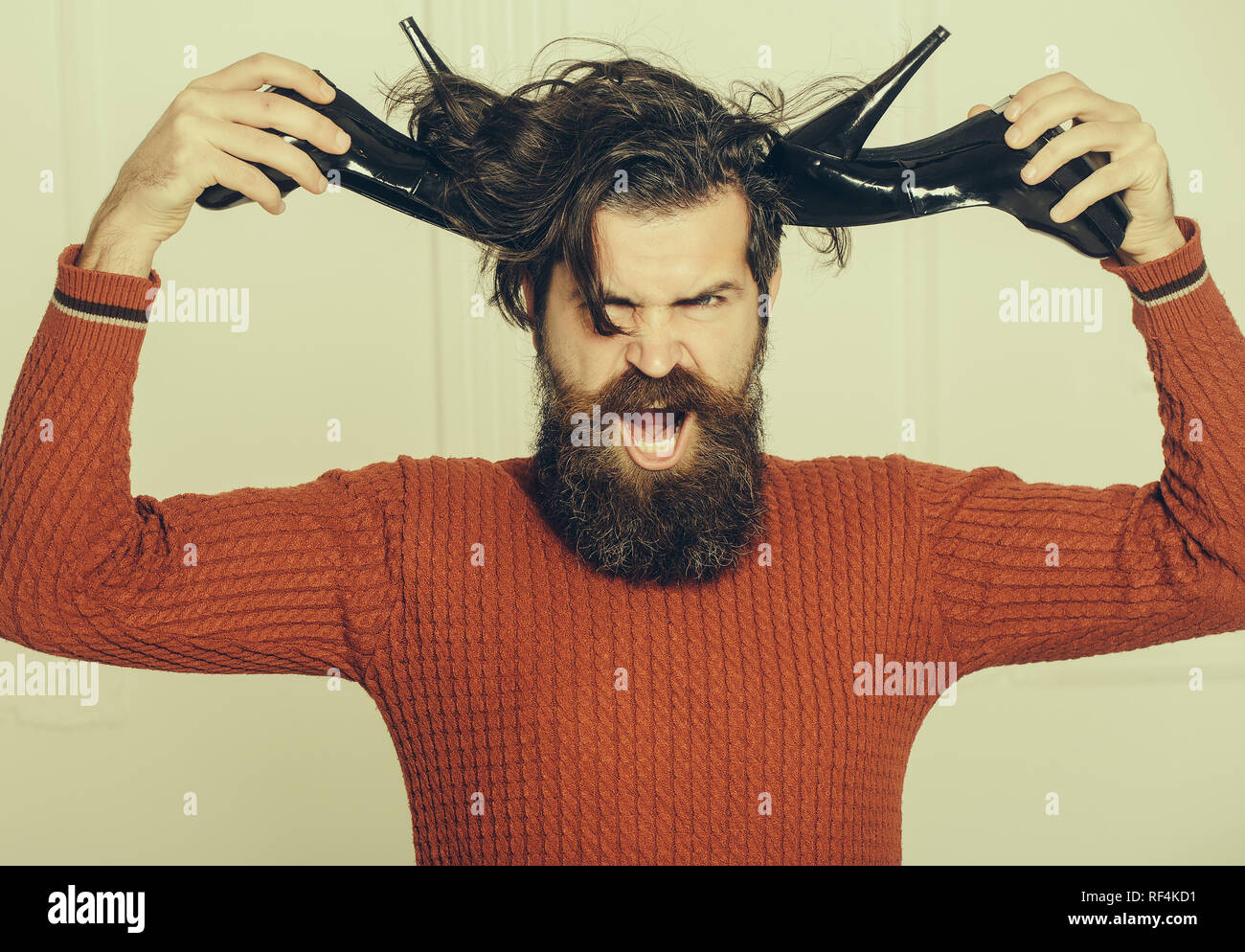 angry bearded man with shoes - Stock Image