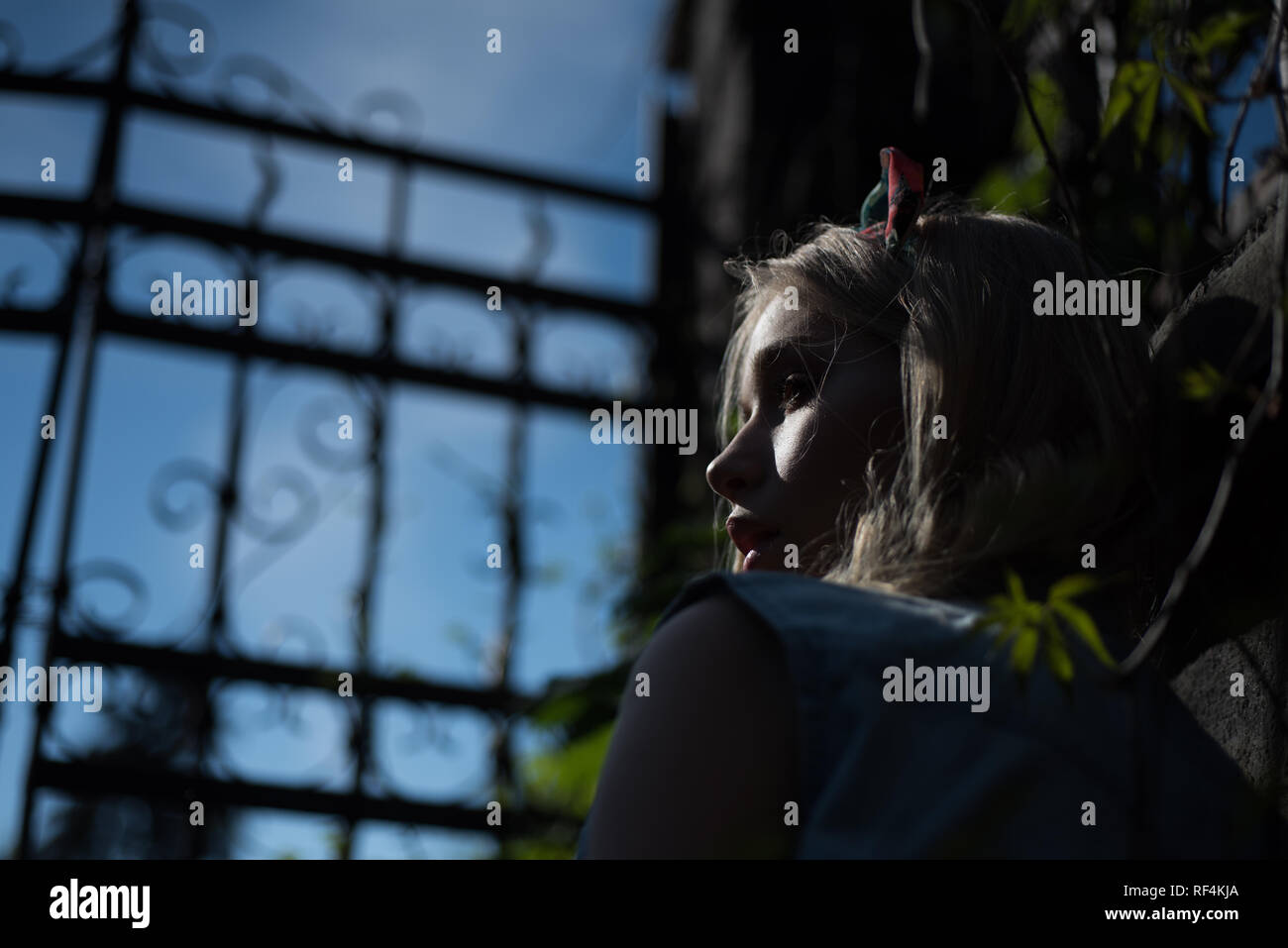 Side view frightened girl wearing headband standing behind tall gate at dusk. Pretty young lady with curled blond hair lost in park at night. Mysteries hidden by darkness Stock Photo