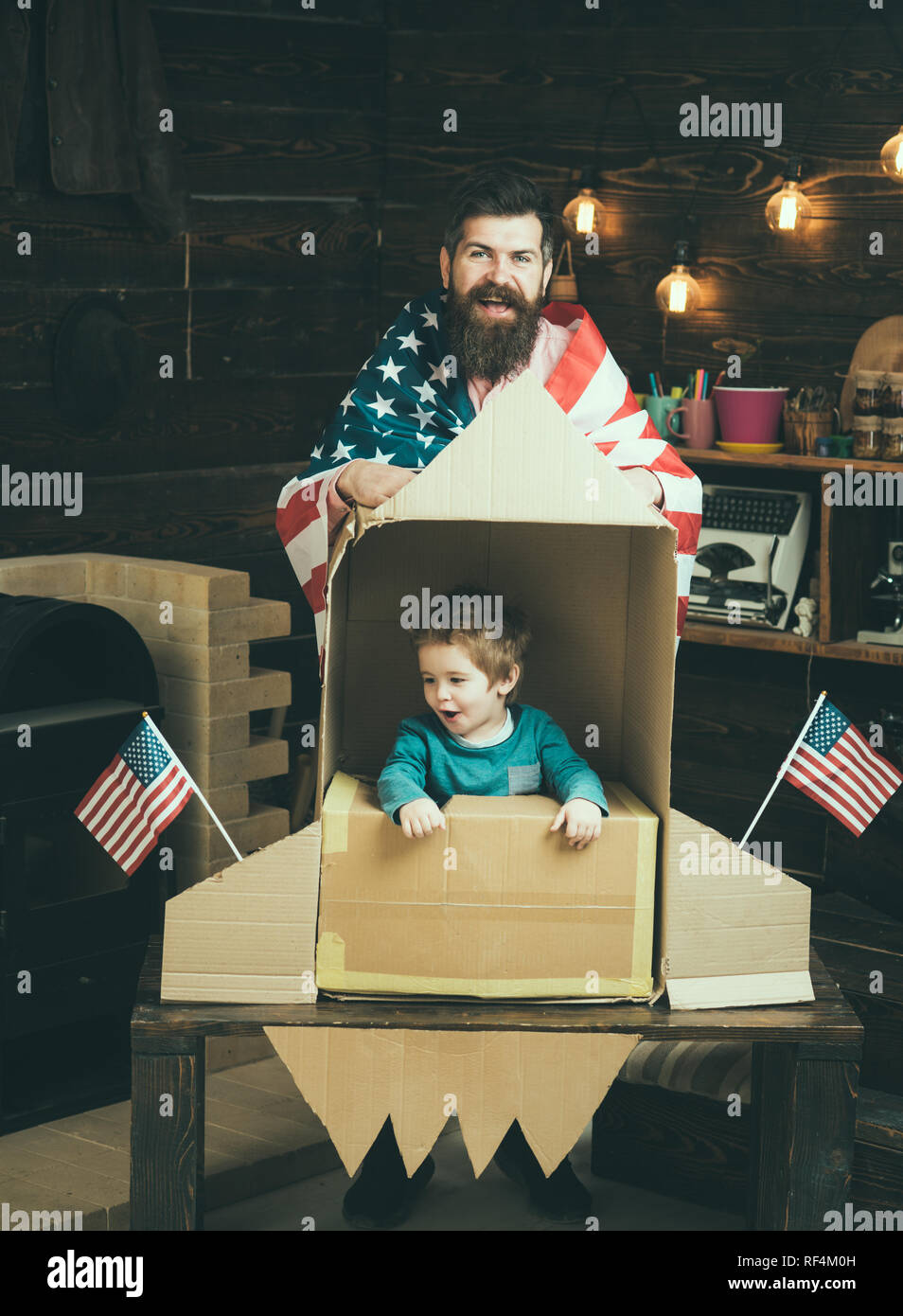 American cheerful family with usa flags play with rocket made out of cardboard box. Child cute boy play cosmonaut, astronaut. Rocket launch concept. Kid happy sit in hand made rocket with usa flags. - Stock Image