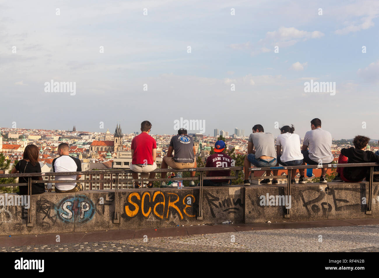Prague, Czech Republic - July 17 2018: People sitting on a fence in Letna Park - Stock Image