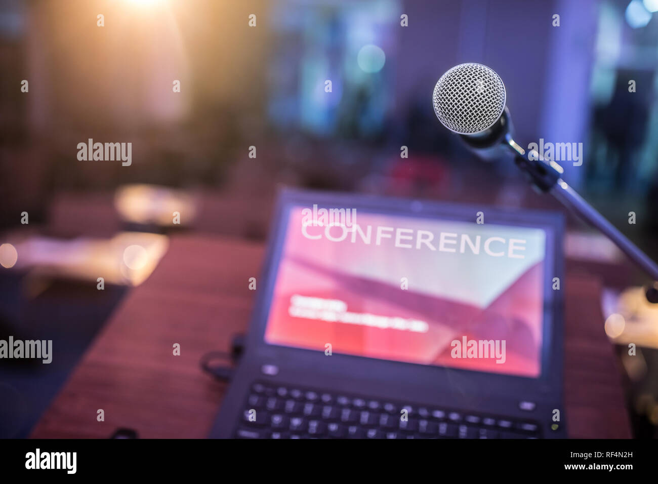 Microphone and laptop computer at podium on business seminar in conference room. - Stock Image