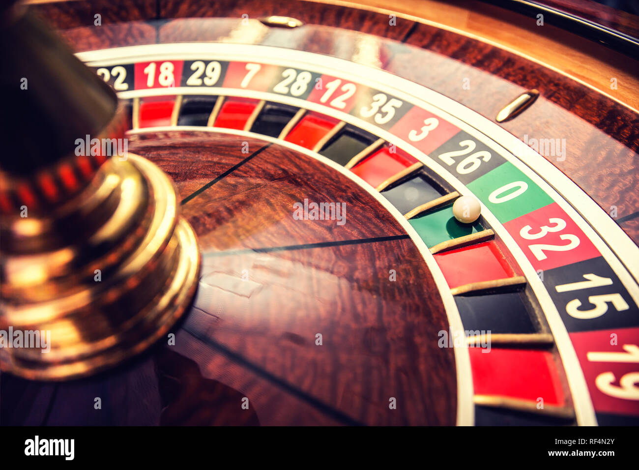Roulette wheel in casino with ball on green position zero. Stock Photo