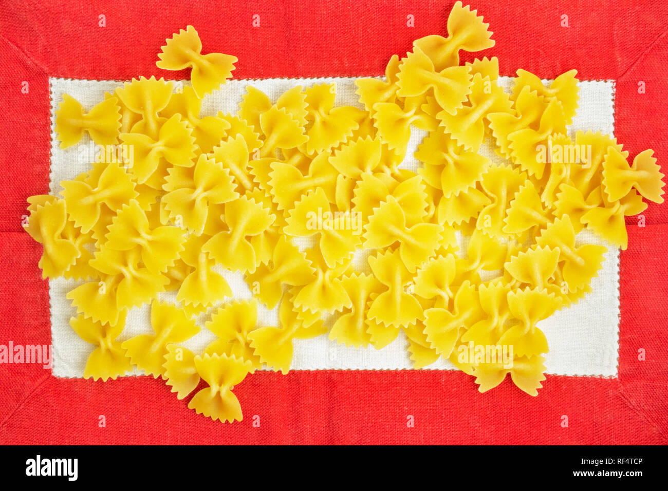 Dry Italian pasta called farfalle on a white-red tablecloth background , beautiful bow tie shape pasta - Stock Image