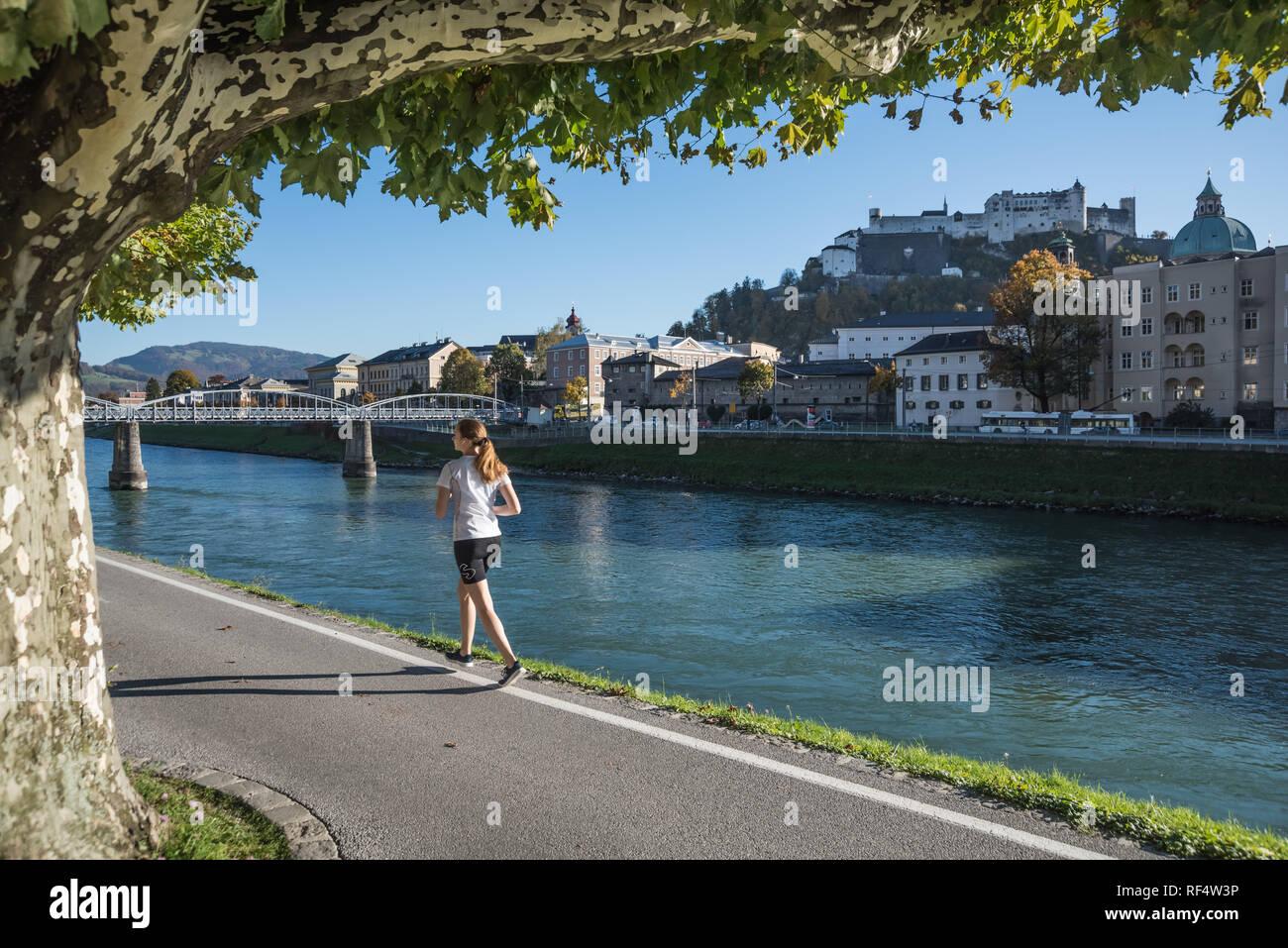 Salzburg, Joggerin an der Salzach, im Hintergrund die Festung Hohensalzburg - Salzburg, Jogging along the Banks of River Salzach, Hohensalzburg Castle - Stock Image