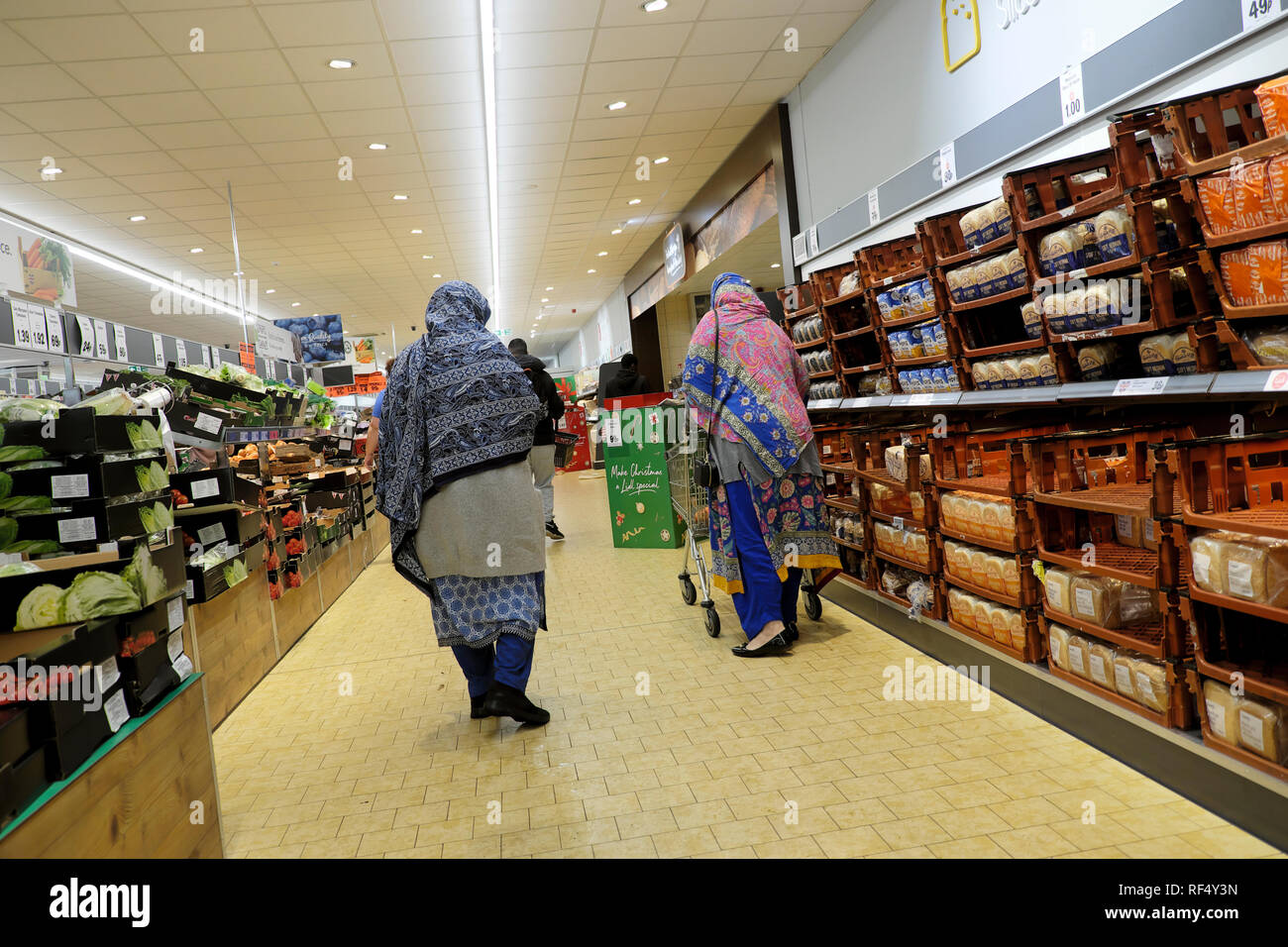 Lidl supermarket shoppers two elderly old women wearing headscarf shopping together in UK  KATHY DEWITT - Stock Image