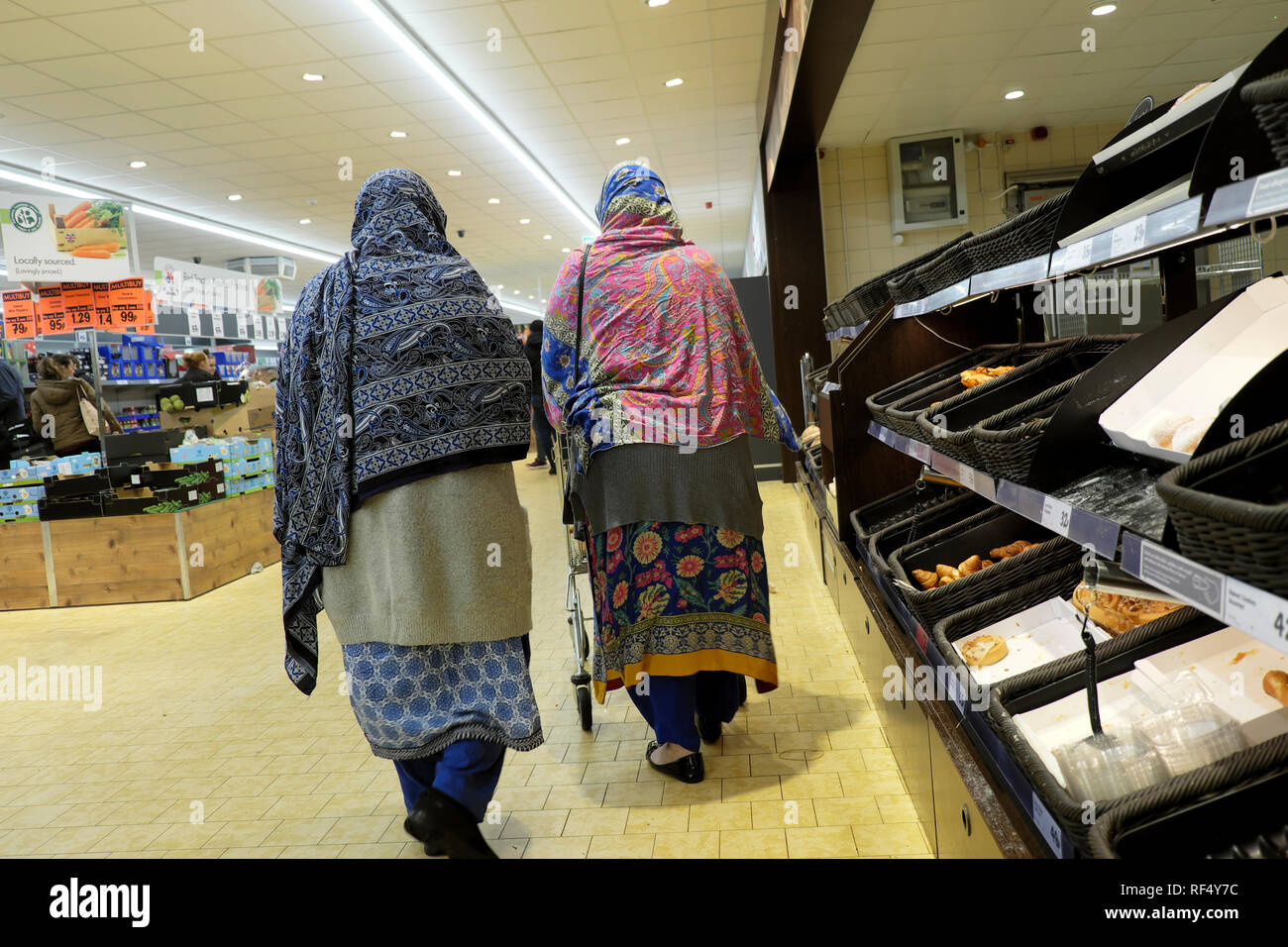 Lidl supermarket shoppers two elderly old women wearing headscarf headscarves shopping together walking past empty bakery shelves in UK  KATHY DEWITT - Stock Image