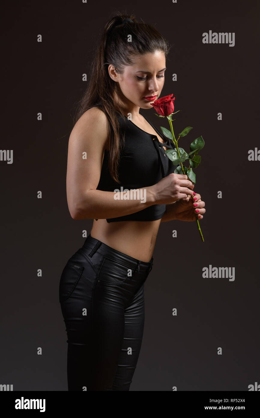 seductive young woman in black clothes smelling red rose Stock Photo