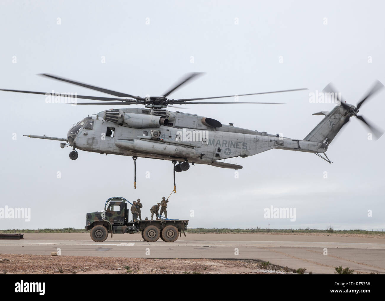 MARINE CORPS AIR STATION MIRAMAR, Calif.- U.S. Marines with 1st Transportation Support Battalion (TSB), 1st Marine Logistics Group (MLG), hook a Medium Tactical Vehicle Replacement (MTVR) to a CH-53E Super Stallion with Marine Heavy Helicopter Squadron (HMH) 462, Marine Aircraft Group (MAG) 16, 3rd Marine Aircraft Wing (MAW) at Marine Corps Air Station Miramar, Calif., Jan. 16. Marines from HMH-462 and 1st MLG conducted an external lift of an MTVR to improve their support capabilities and exercise the aircraft's limit of 36,000 pounds. (U.S. Marine Corps photo by Lance Cpl. Clare J. McIntire) Stock Photo