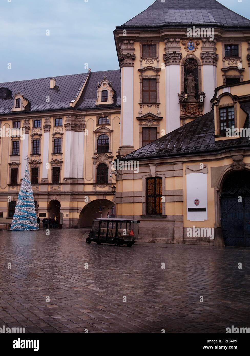 Baroque Architecture and Christmas Tree and Light Snow and a Group of Tourist with a Guide - Stock Image