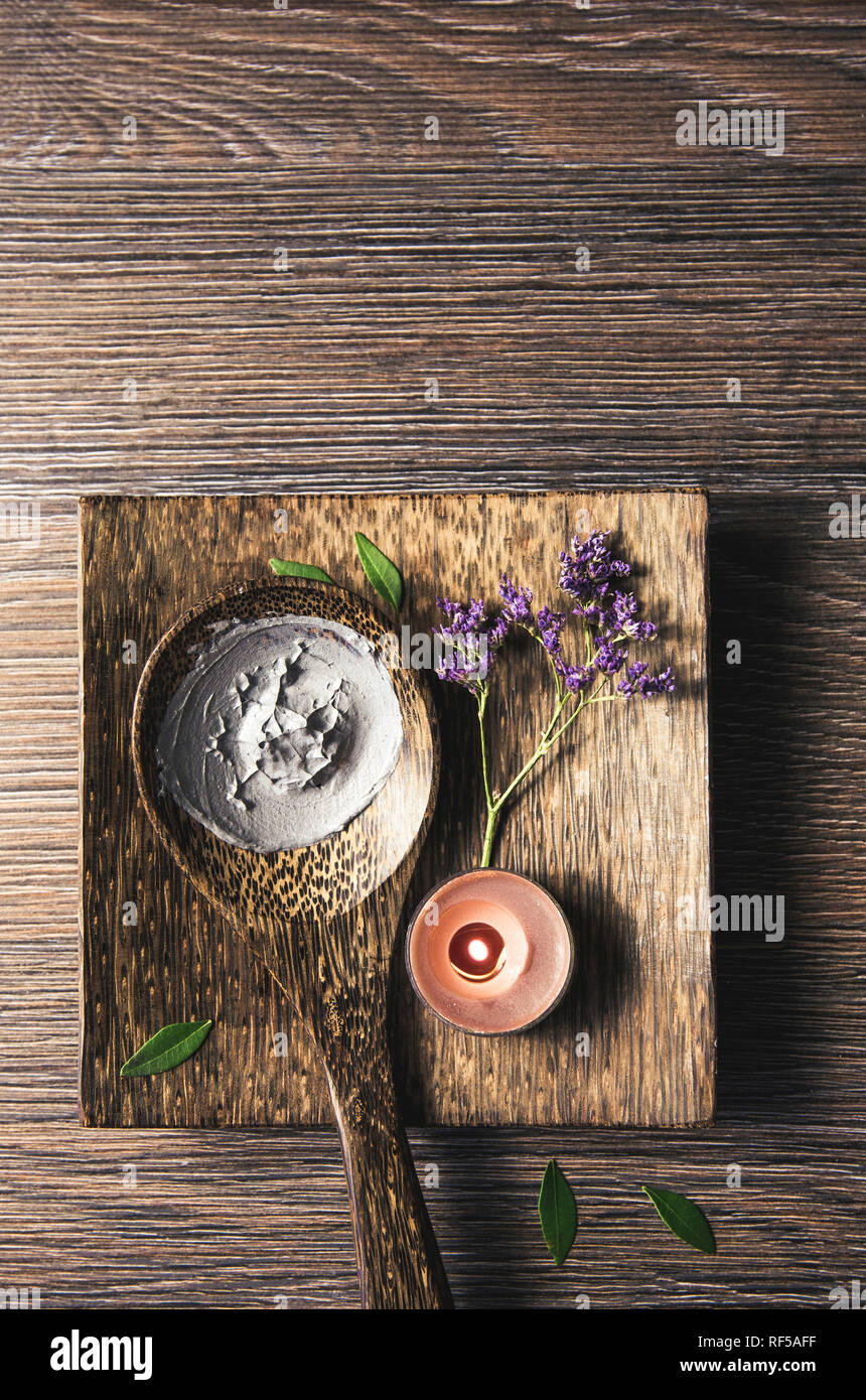 Natural gray mud mask cream on wooden spoon with candle