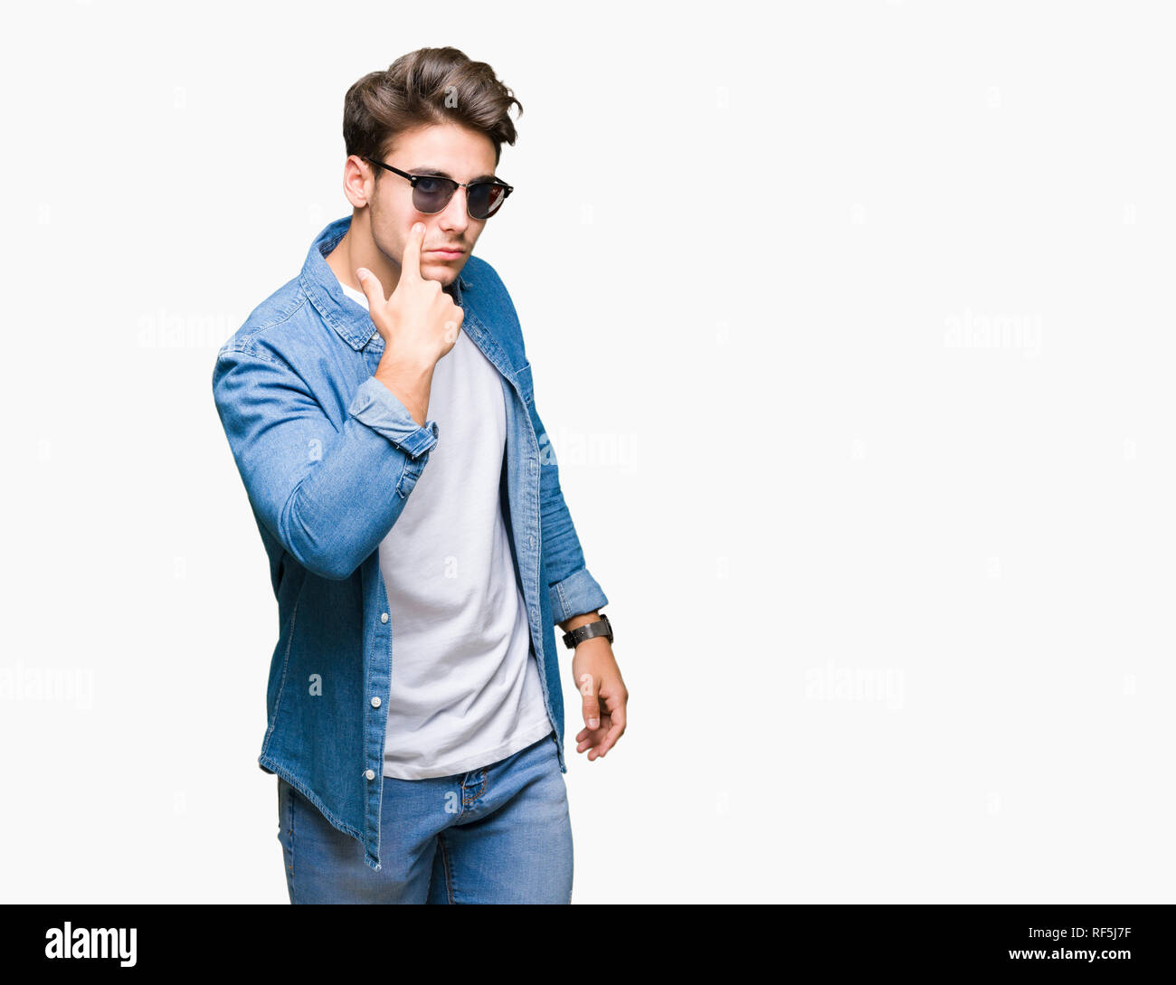 729a3c6cb3c Young handsome man wearing sunglasses over isolated background Pointing to  the eye watching you gesture