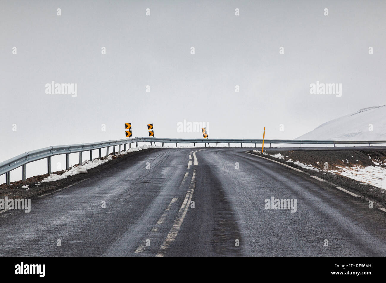 Through the windscreen shot of a tarmac road in East Iceland in foggy weather conditions. - Stock Image