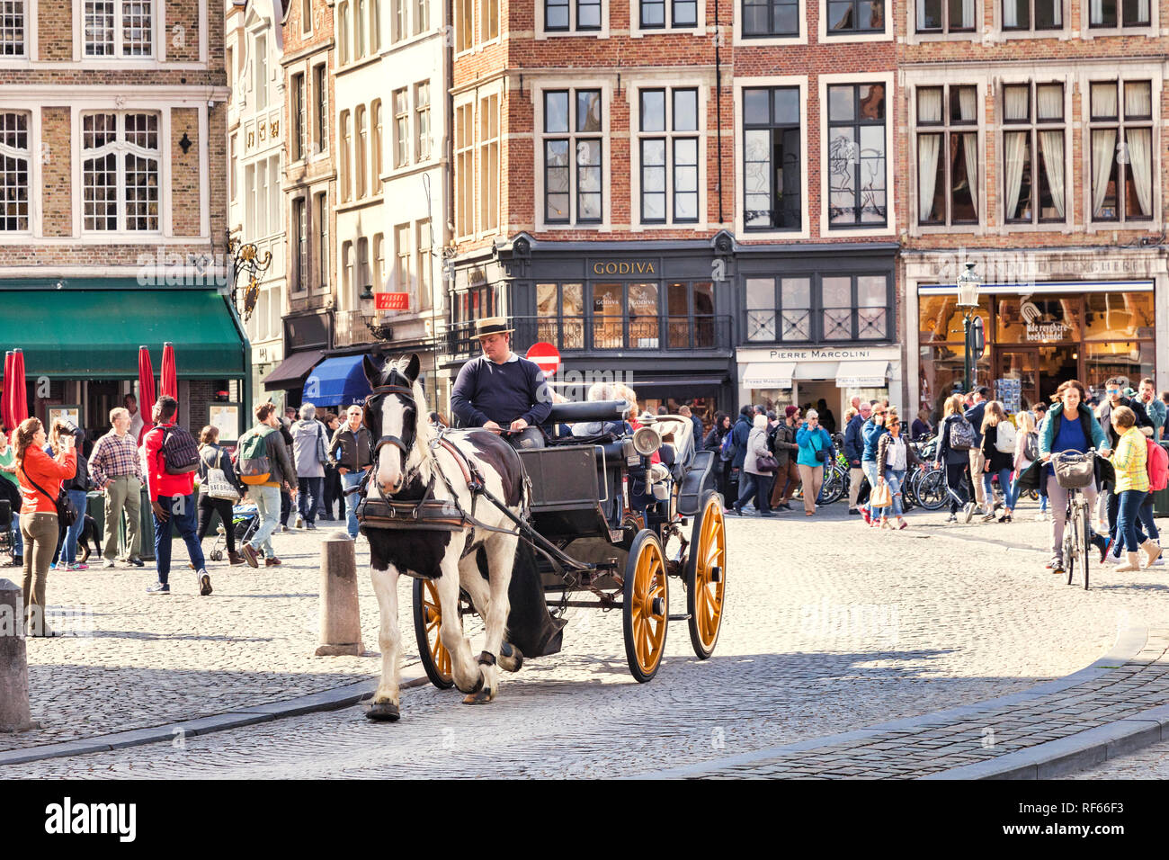 25 September 2018: Bruges, Belgium - Horse and carriage ride in beautiful and historic central Bruges, with tourists taking photos on a sunny autumn d Stock Photo