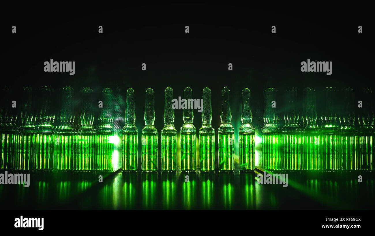 concept of development of the production of medical products. Bright vials with luminous green contents: Poisons, doping, Acid, chemistry, antibiotics - Stock Image