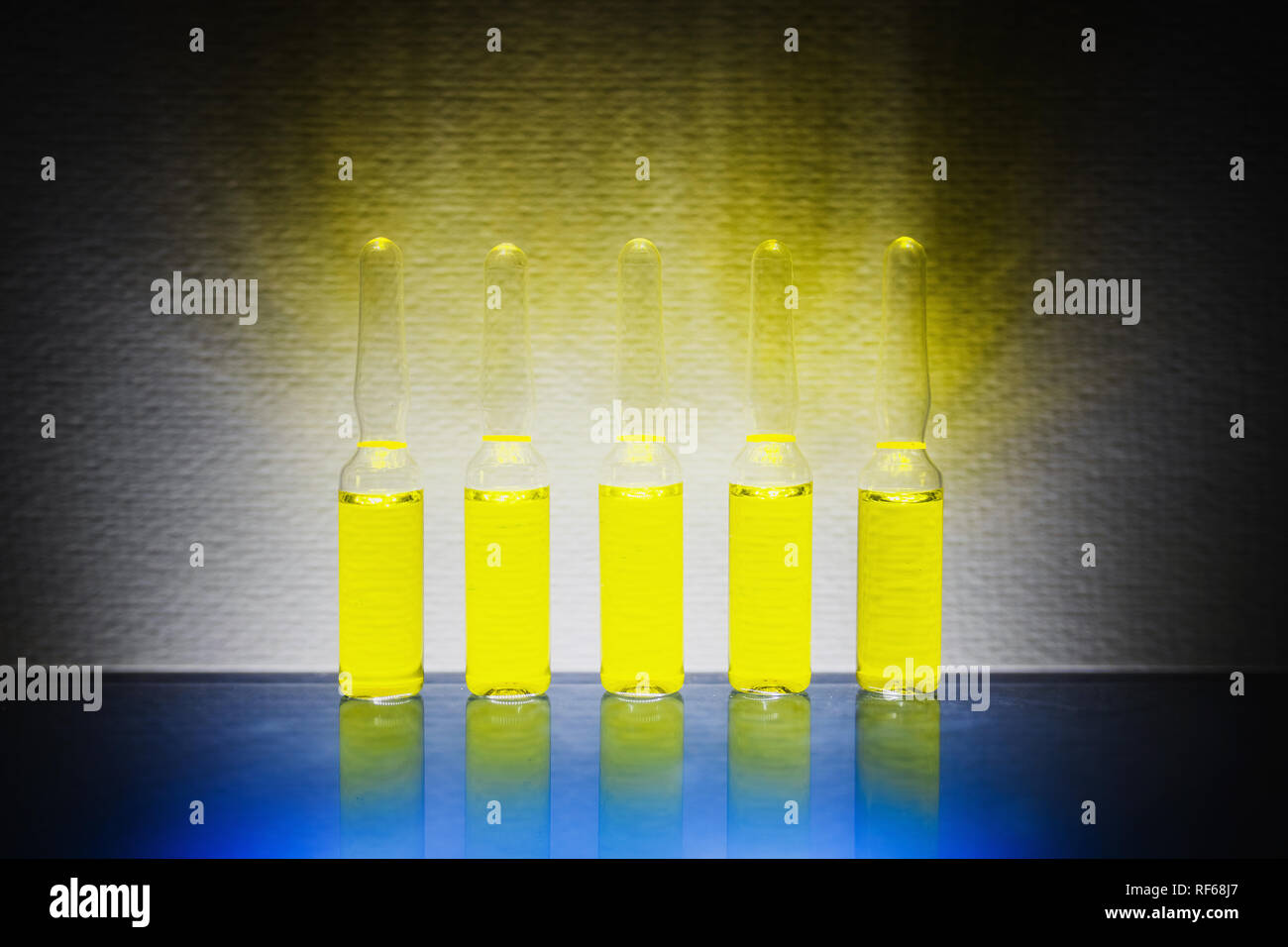 yellow narcotic drugs, chemicals, vitamins in ampoules on a white background. Stock Photo