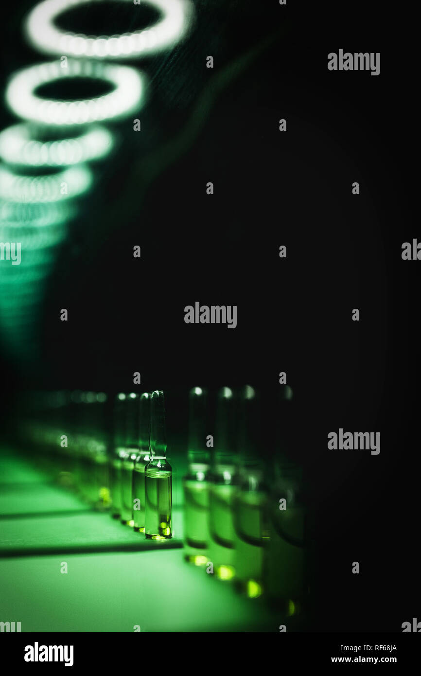 The concept of clandestine drug production. Liquid in ampoules in an endless row of conveyors. Theft of drugs in the enterprise. artistic dark filter. - Stock Image