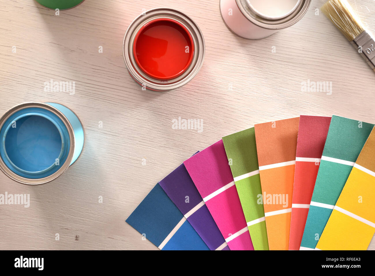 Colorful paint pots open and color palette on white table for renovation of materials. Top view. Horizontal composition. Stock Photo