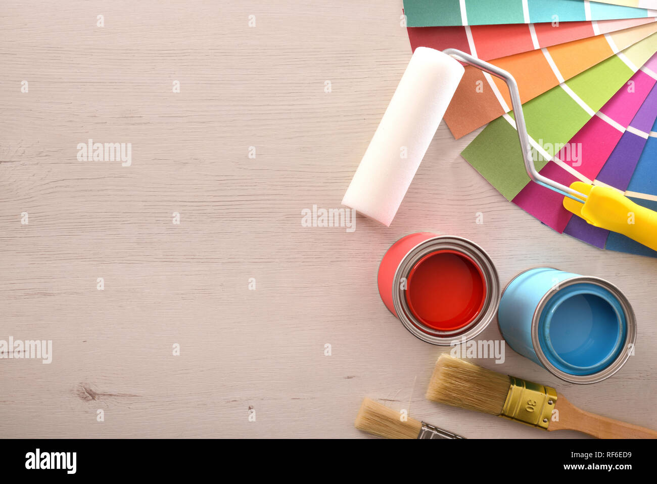 Two red and cyan paint pots open and color palette on wood table for renovation of materials. Top view. Horizontal composition. Stock Photo