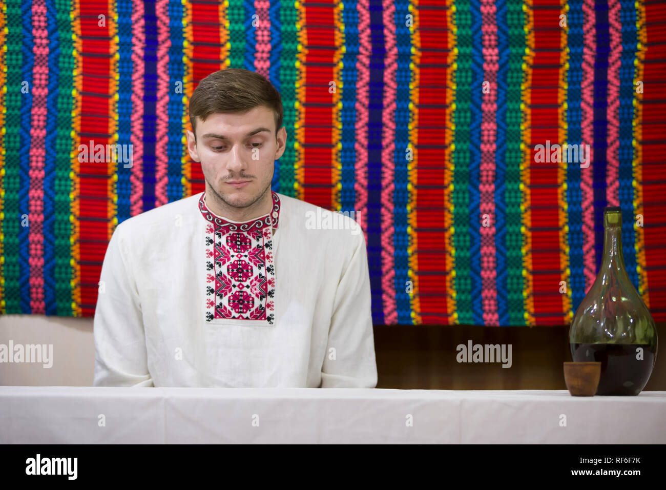 Reconstruction of an ethnic old Belarusian wedding.Ukrainian man in embroidery with a bottle of moonshine sitting a - Stock Image