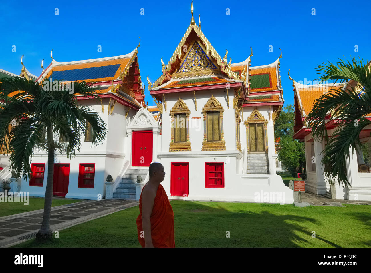 A monk passes prettily restored clerical buildings on the  grounds of Wat Boworniwet, Bangkok, Thailand, also known as Marble Temple - Stock Image
