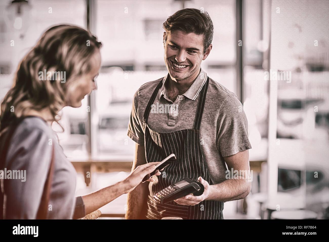 Woman paying bill through smartphone using NFC technology Stock Photo
