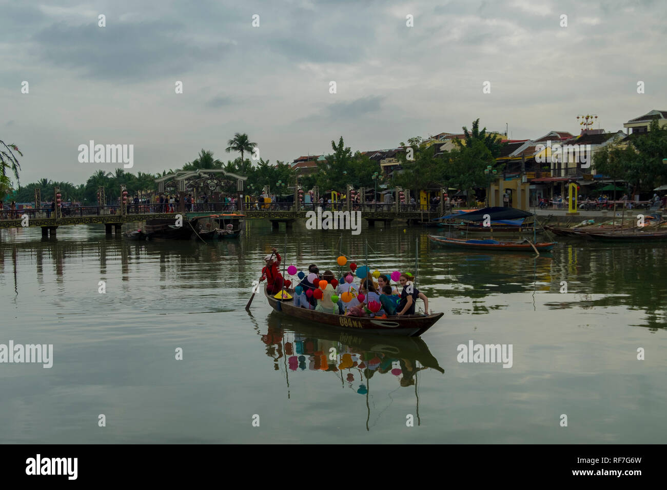 Small boat plying the Thu Bon River in Hoi An, Vietnam. - Stock Image