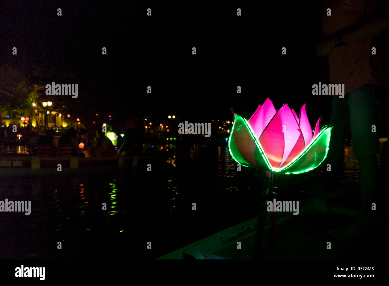 Boats drift along the lovely Thu Bon river as the night is lit by lanterns in Hoi An, Vietnam. - Stock Image