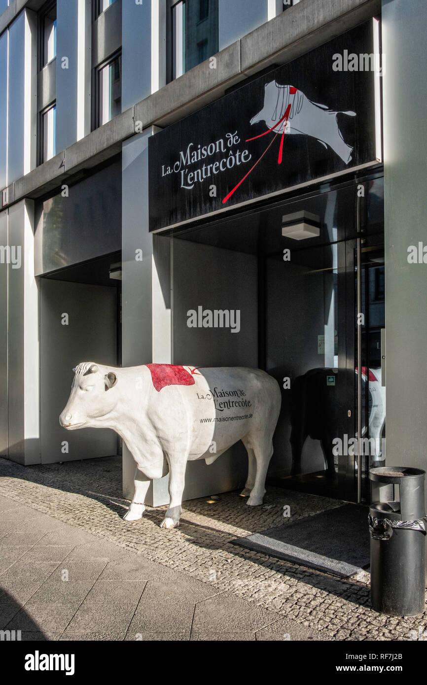 Berlin, Mitte. La Maison de L'entrecote restaurant & steakhouse at Hotel Indigo,Statue of cow at entrance - Stock Image