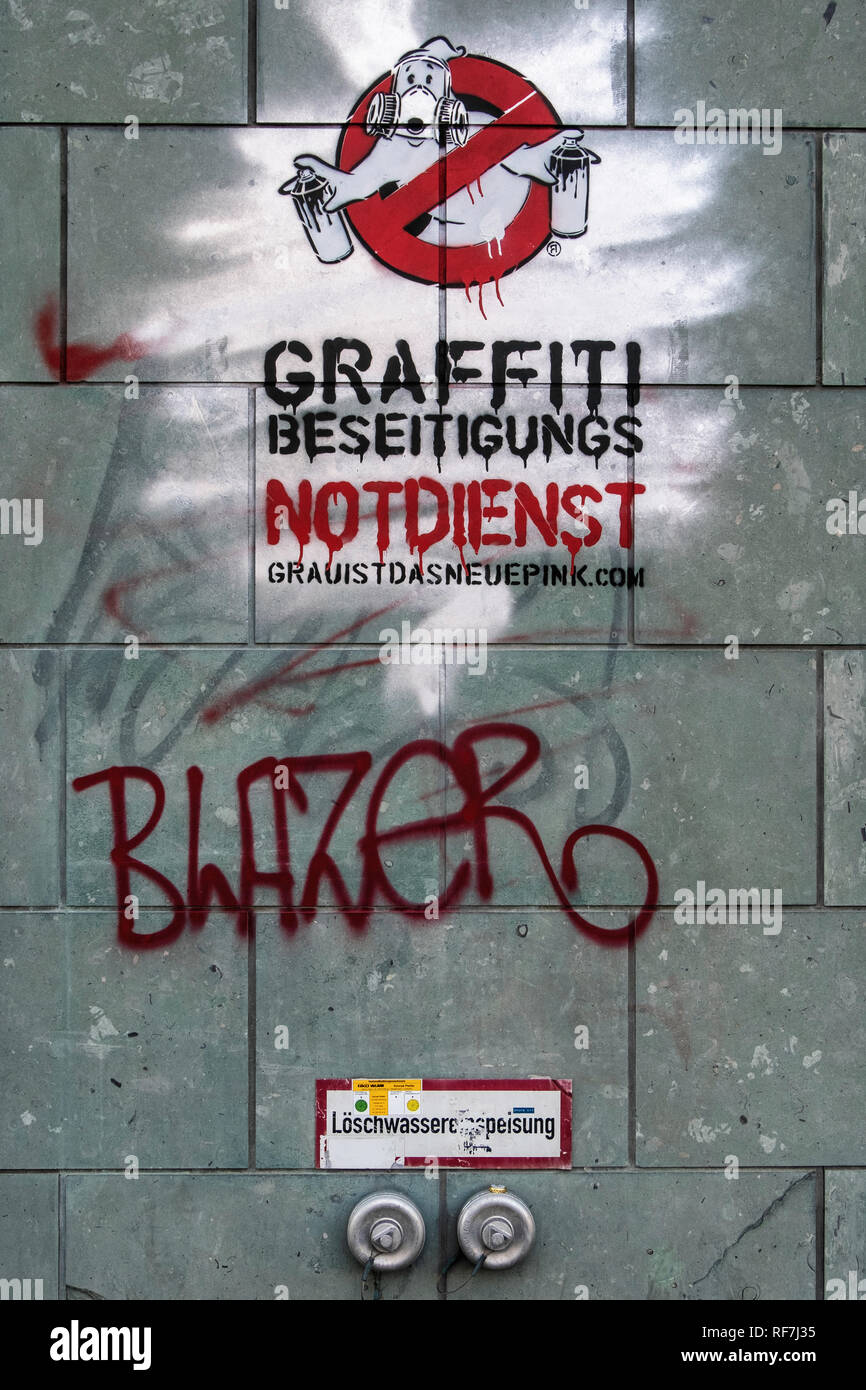 Berlin Street art. Graffiti removal Emercency service stencil by artist Ostap on graffiti covered wall - Stock Image