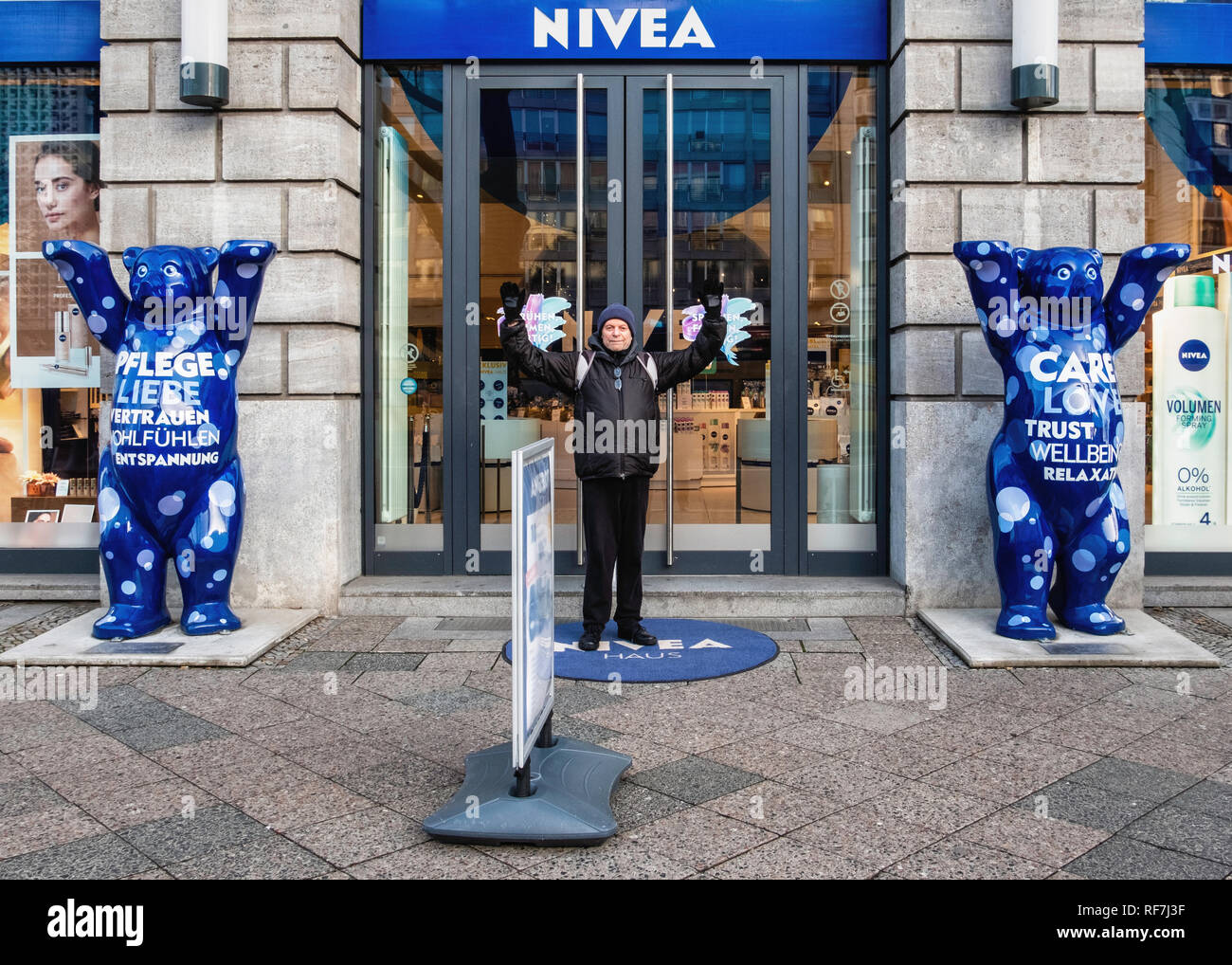 Berlin,Mitte. Elderly male tourist mimics two blue Buddy Bears outside Nivea Shop in Unter den Linden Stock Photo