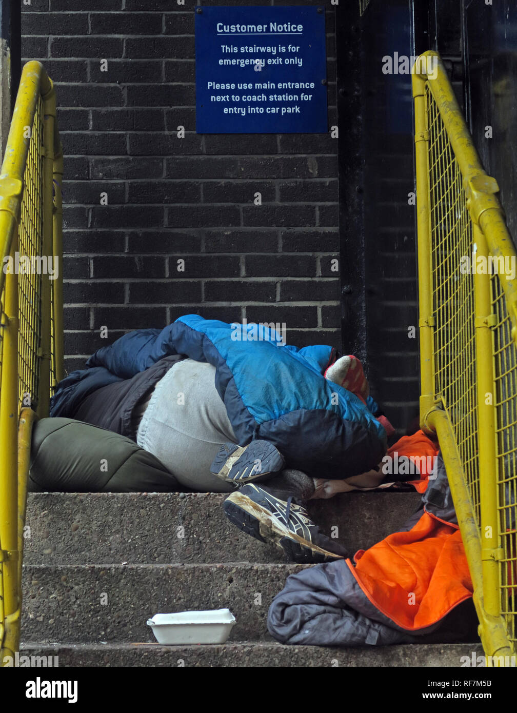 Homeless person sleeping rough, in a car park stairwell, Bus station,Chorlton St, Manchester, M1 3JF - Stock Image