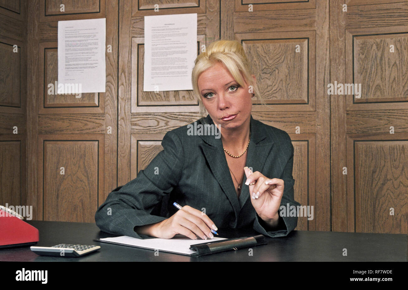 Businesswoman sitting behind desk in wood panelled office - Stock Image