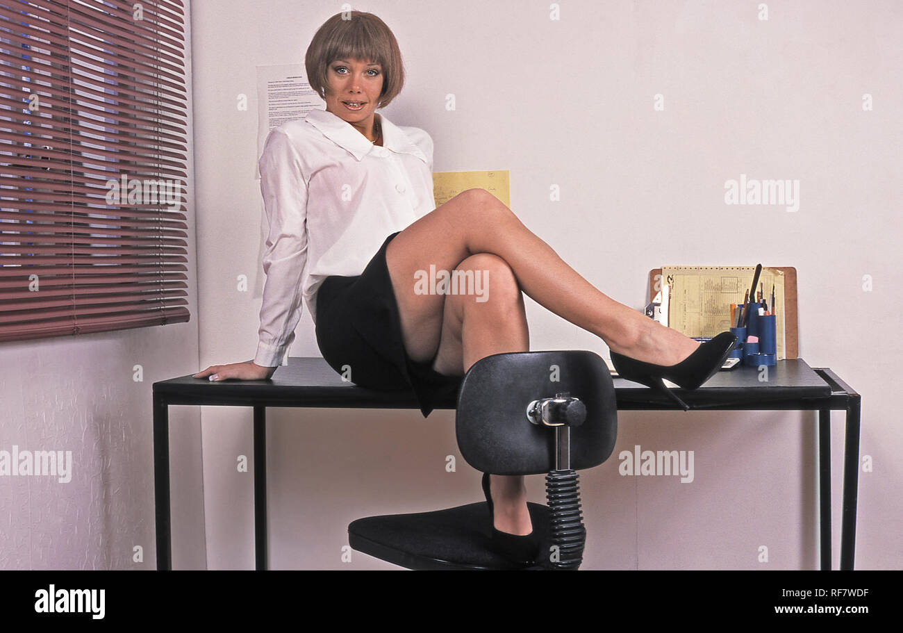 Female office worker sitting on desk with one foot on desk and one foot on chair Stock Photo