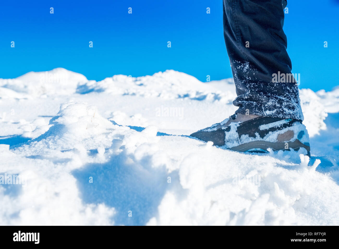 Close up shot of  (female) winter walker's boot in snow on the approach to Kinder Scout in the Peak District, UK - Stock Image