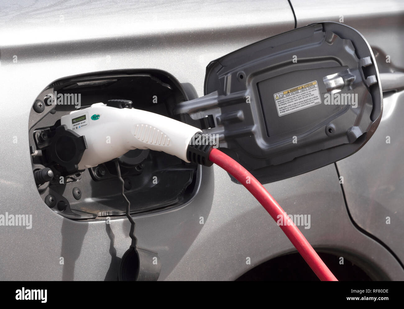 Close up of an electric car being charged. - Stock Image
