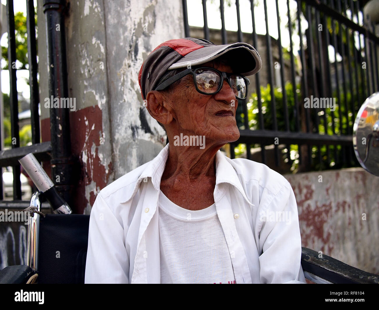 CAINTA, RIZAL, PHILIPPINES - JANUARY 17, 2019: A man with disability sits in his wheelchair and looks at the camera. - Stock Image