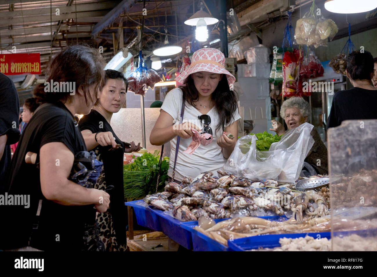 Thailand food market. Japanese tourists buying from a seafood stall. Na Klua fish market, Pattaya Thailand Stock Photo