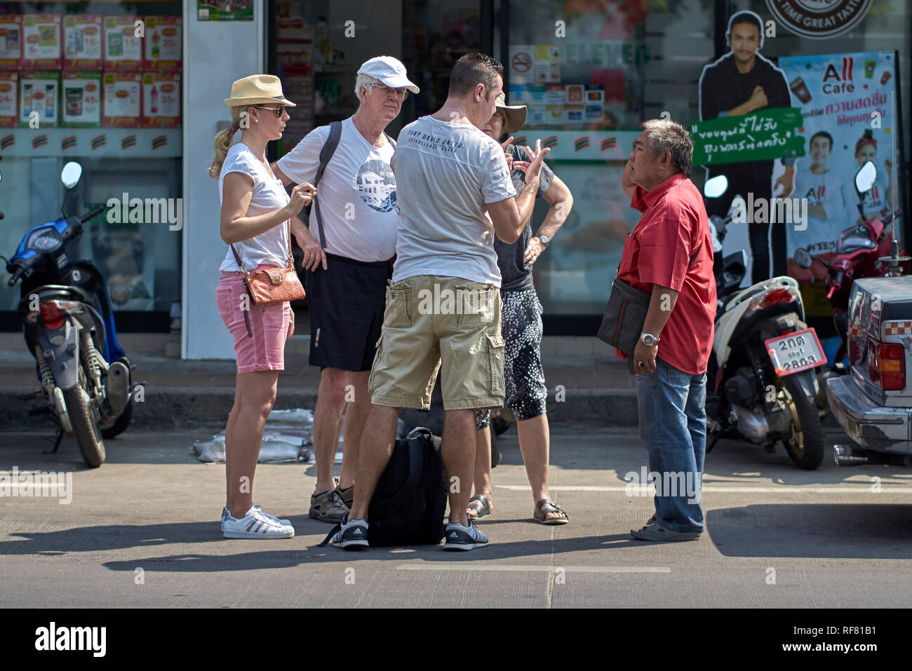 Thailand tourists negotiating fare with Thai taxi driver using fingers to talk. - Stock Image