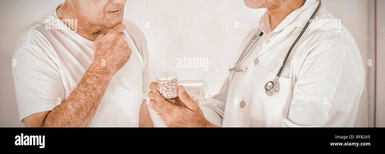 Male doctor advising senior man on medical prescriptions - Stock Image