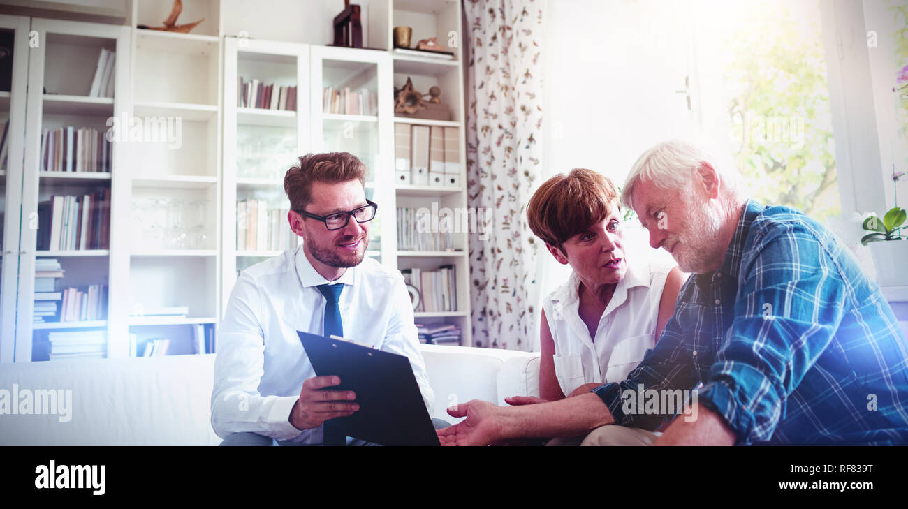 Senior couple planning their investments with financial advisor - Stock Image