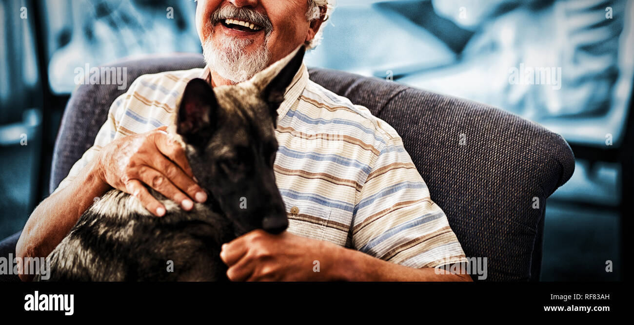 Portrait of smiling senior man sitting with puppy on chair - Stock Image
