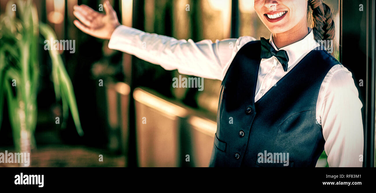 Portrait of smiling waitress welcoming - Stock Image