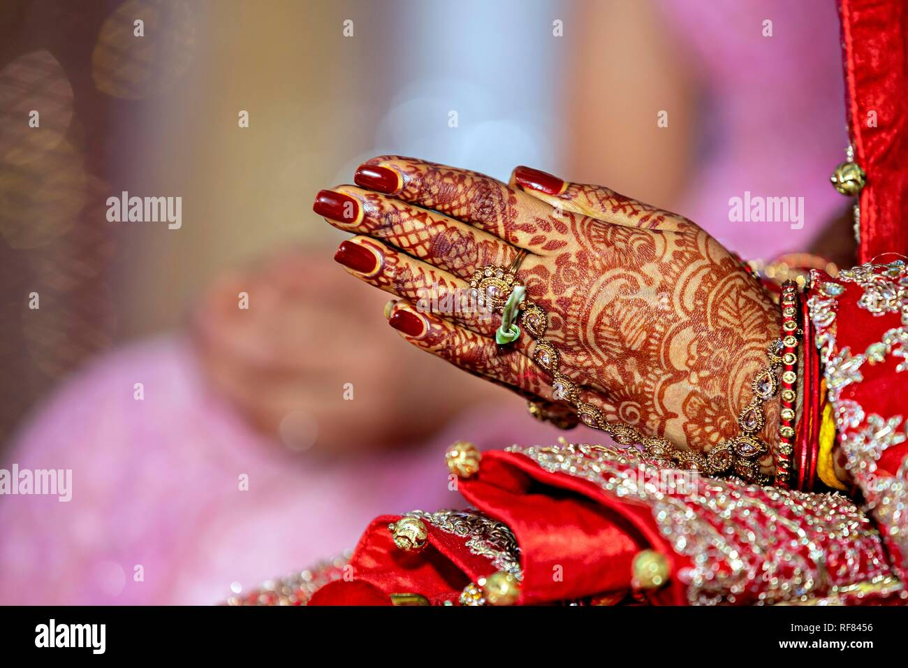 Traditional bridal jewelry and henna decoration on the hands of the bride during a religious ceremony at a Hindu wedding Stock Photo