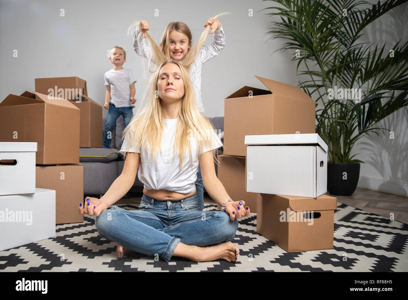 Photo of calm blonde sitting on floor among cardboard boxes and boy, girl jumping on sofa in new apartment - Stock Image