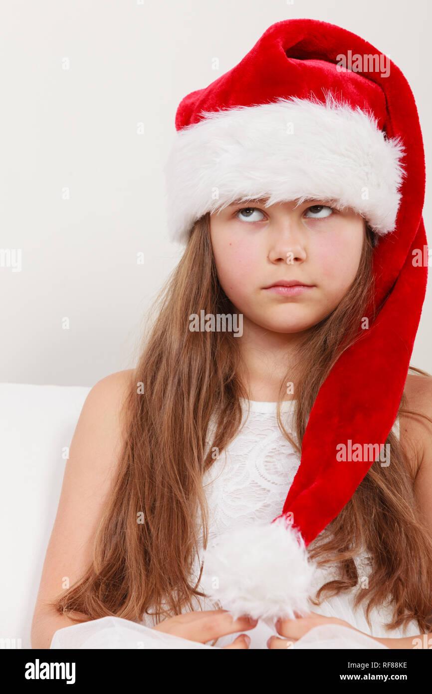 2919da18f082d Bored cute little girl kid in red santa claus hat and white dress.  Chrtistmas holiday season.