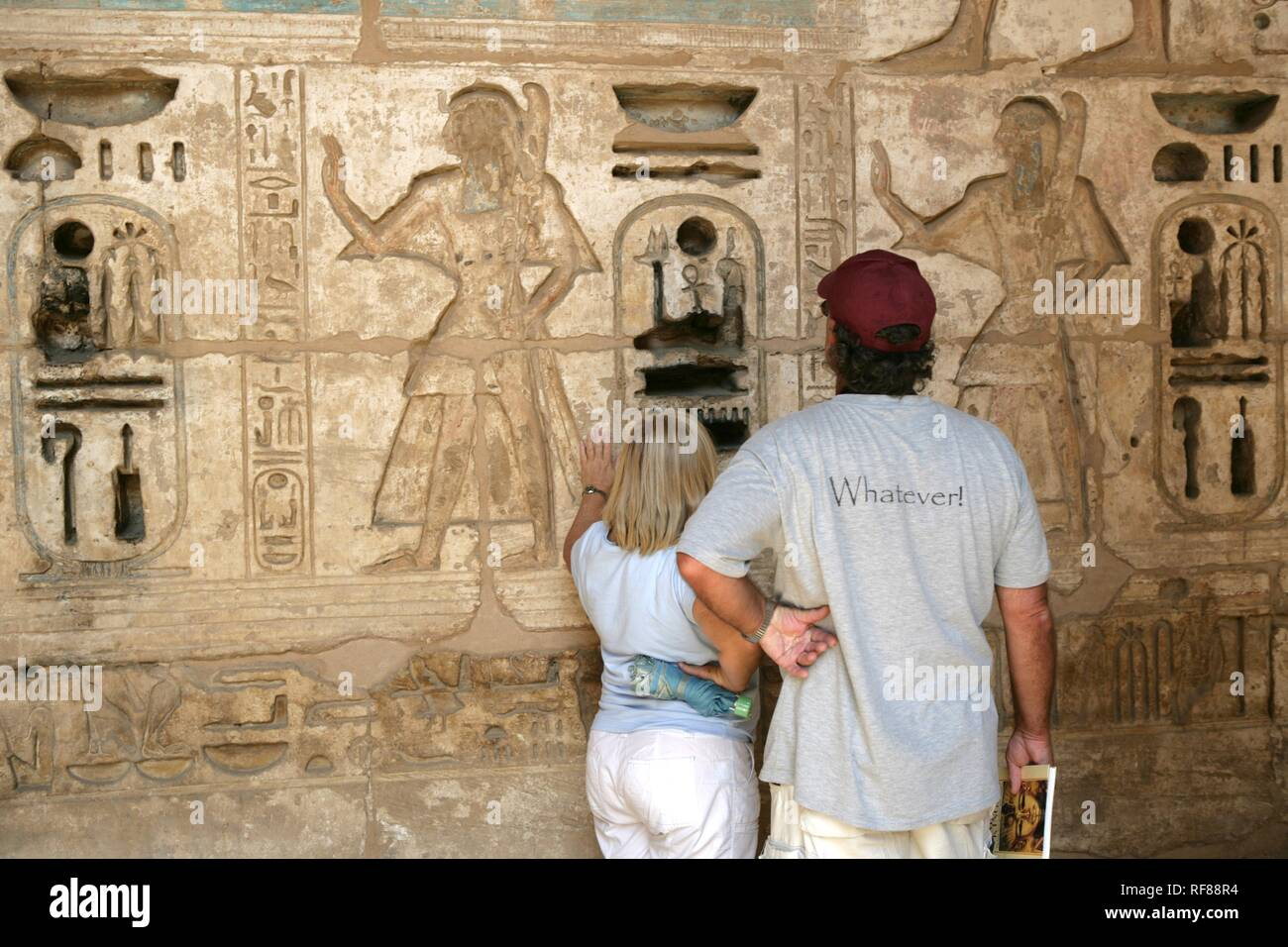 Tourists looking at hieroglyphs, Medinet Habu, Mortuary Temple of Ramesses III, West Thebes, Luxor, Egypt, Africa Stock Photo