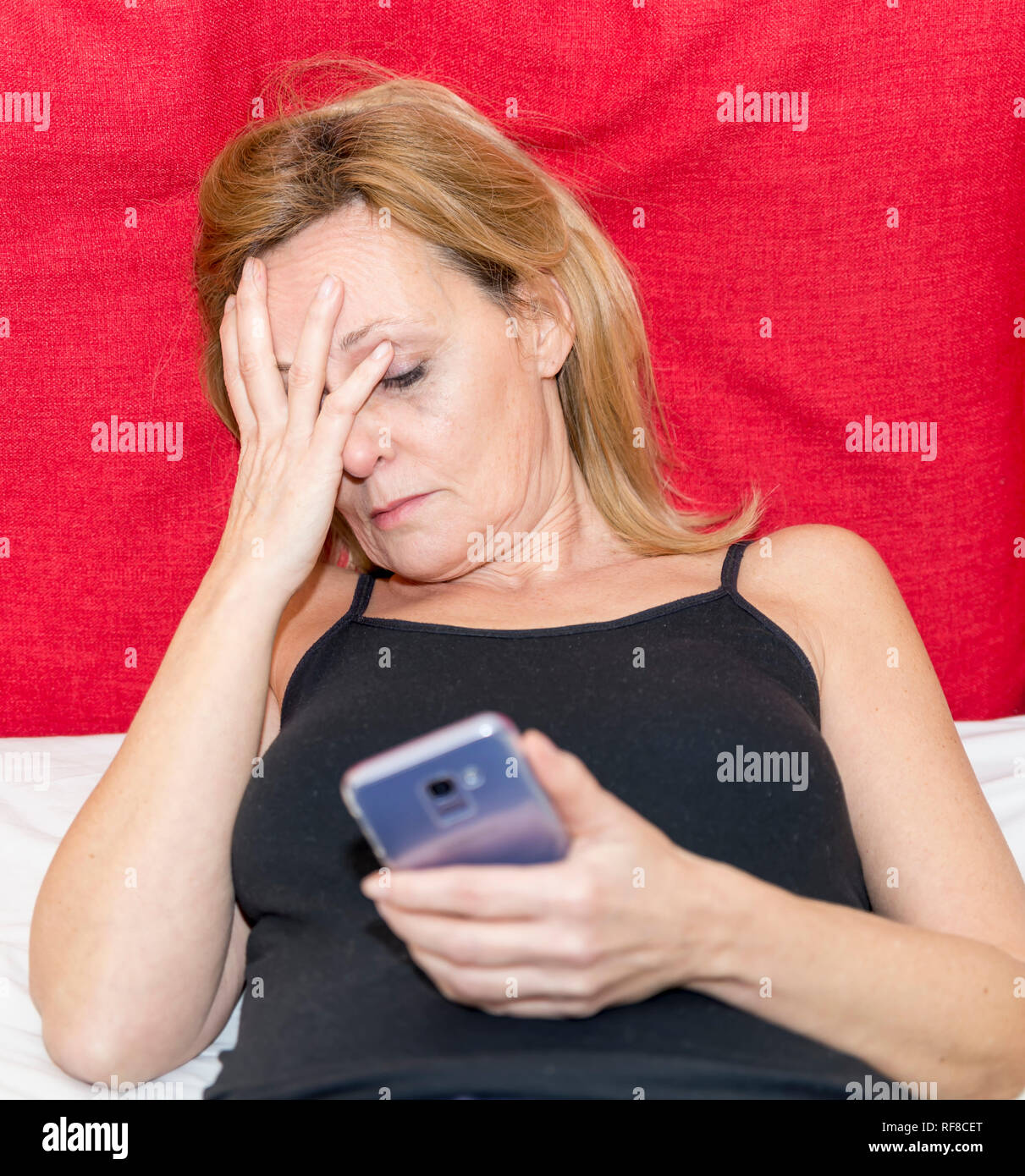 Desperate woman covers her face with one hand while in the other she holds a smartphone - Stock Image