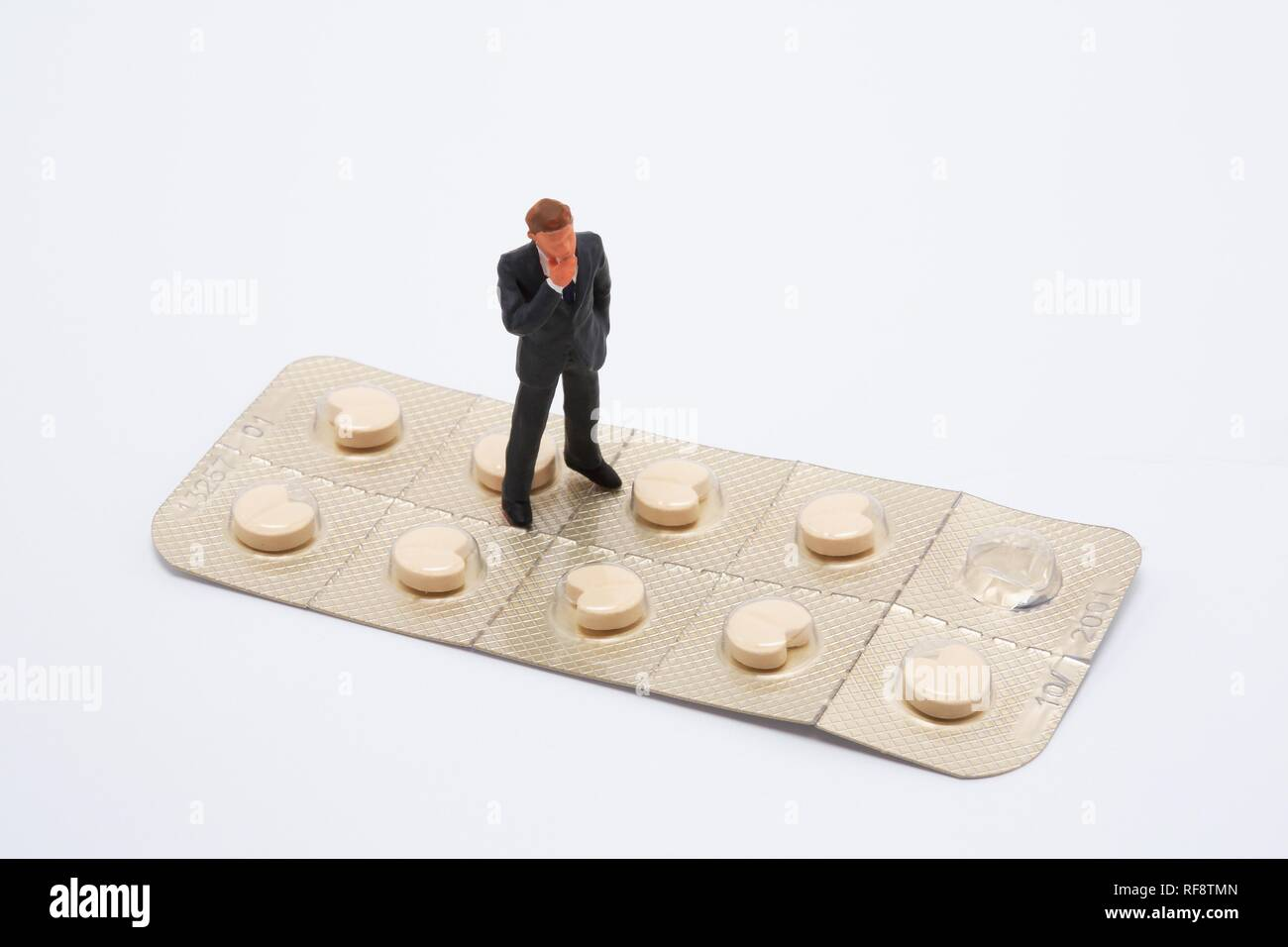 Small man standing on a large pill packet (beta blockers): symbol for skepticism of the pharmaceutical industry Stock Photo