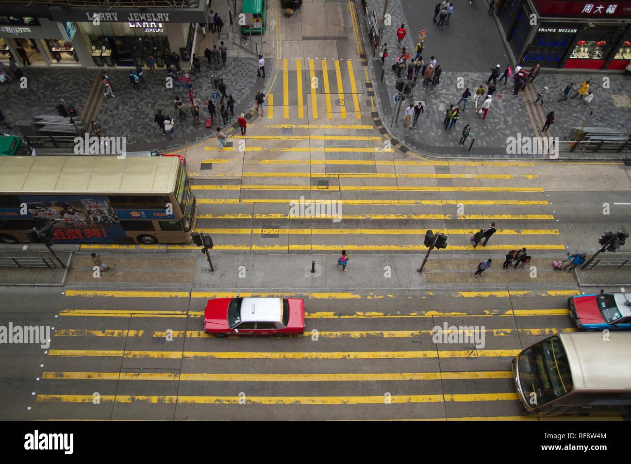 High view down to street crosing yellow markings Hong Kong - vehicles cars below - Stock Image