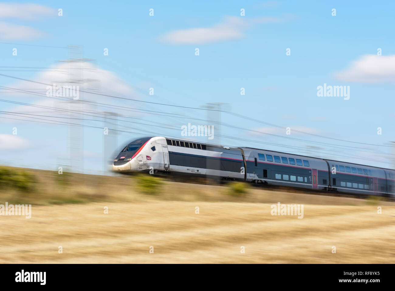 A TGV Duplex high-speed train in Carmillon livery from french company SNCF driving at full speed on the East European high-speed line. - Stock Image